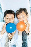 Two businessmen blowing up balloons, portrait