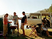 Family camping by lake, woman tending barbecue grill