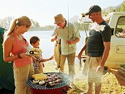 Three generational family gathered by barbecue grill, by lake