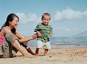 Woman on beach with baby boy (16-19 months), smiling, portrait