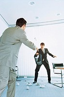 Businessman throwing crumpled paper at colleague holding waste bin