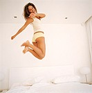 Young woman jumping on bed, smiling, portrait