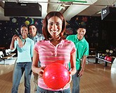 Friends watching young woman holding bowling ball, smiling, portrait