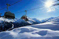 Four skiers in ski lift above snow slope
