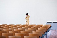 Man standing at head of empty conference hall, rubbing temple