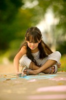 Girl (6-8) drawing on sidewalk with chalk