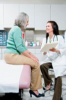 Female doctor discussing file with senior female patient, smiling