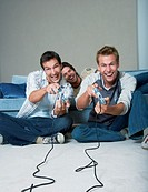 Young men relaxing in living room, two playing video game