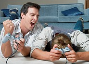 Young men lying on living room floor, playing video game
