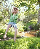 Boy (5-7) sitting on rope swing, smiling, portrait