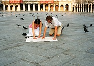 Italy, Florence, couple kneeling in square, looking at map