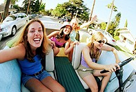 Group of women in convertible car, smiling
