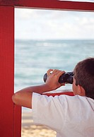 Boy (6-8) looking out to sea through binoculars, rear view