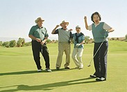 Four mature golfers standing on golf course, cheering