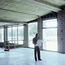 Man looking at blue print, standing in empty retail space