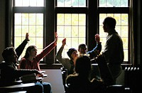 Students raising hands in college class