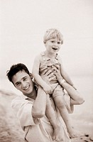 MAN HOLDING BOY ON SHOULDER AT BEACH