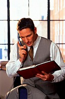 Businessman on telephone looking at day planner