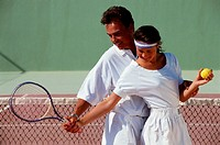 Man teaching woman to play tennis