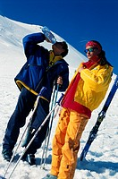 Couple with ski pole, man drinking water