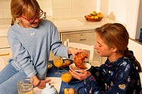 Two girls in kitchen having breakfast