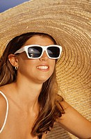 Young woman with sunglasses and straw hat