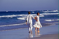 Couple wearing white walking on beach