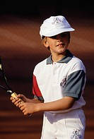 Young boy (8-9 ) holding tennis racket