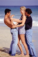 Two young men and young woman playing at beach, side view