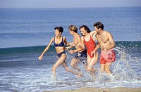Four young people running along beach