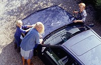 Two women and girl (8-9) washing car, portrait, elevated view