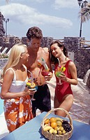 Three young people wearing swimsuits holding exotic drinks