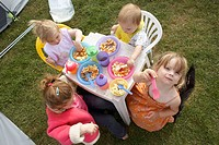 4 children camping, sitting round a table eating dinner
