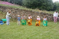 Group of pre school children doing a sack race on sports day