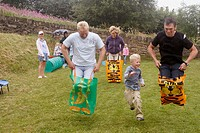 Group of dads on sports day, doing the sack race