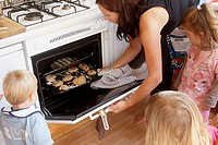 Mother baking with a group of children, putting the bread in the oven.