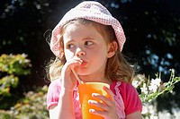 3 year old girl sitting on a wall outside, drinking orange through a straw