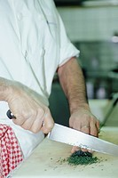 Chef dicing herbs on chopping board, close-up of hands and knife