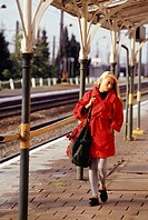 Woman walking on platform by train tracks, full length