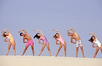 Group of young people doing aerobics on beach