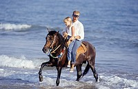 Father and teenage daughter (13-14)  riding horse on beach
