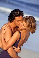Couple embracing, kissing on beach