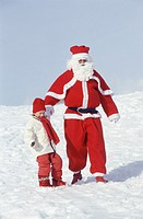 Santa Claus walking down hill with girl (4-5 years), front view