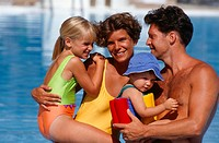 Family with baby (9-12 months) and girl (8-9) embracing near pool