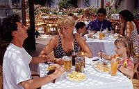 Parents with daughter (4-5) sitting at table in outdoor restaurant