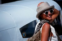Woman wearing sunglasses by air craft