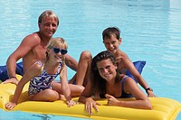 Family sitting and leaning on airbeds, in swimming pool, portrait