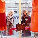 Women window shopping, looking at handbag