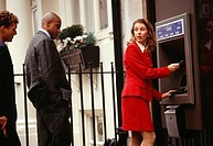 Businesswoman using ATM in street