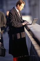 Businessman using laptop on bridge